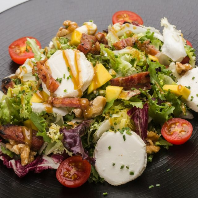 Salad with goats cheese, mango, bacon, walnuts and soft mustard dressing